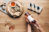 """Постер, картина, фотообои """"частичный вид сомелье проведение бутылку вина за столом с бокалами, едой и столовыми приборами"""""""