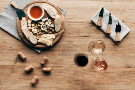 Photo for Top view of wine glasses, sauce, bread, cheese, olives, corks and cooking utensils on wooden surface - Royalty Free Image