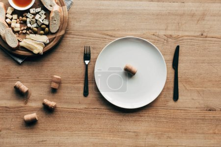 Photo pour Vue supérieure de l'assiette avec le liège, les couverts et la nourriture sur la table en bois - image libre de droit