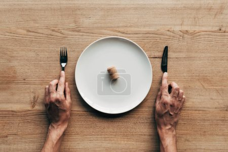 Photo for Cropped view of man holding fork and knife at table with plate and cork - Royalty Free Image