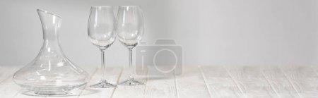 Photo pour Coup panoramique de verres à vin vides et cruche sur la surface en bois - image libre de droit
