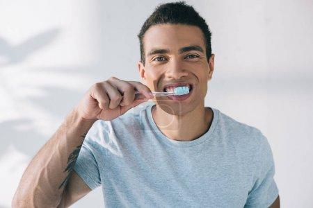 Photo pour Jeune homme brossant des dents avec la brosse à dents et regardant l'appareil-photo - image libre de droit
