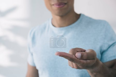selective focus of man holding contact lens on finger