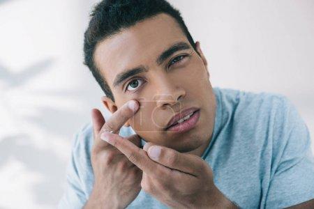 Photo pour Jeune homme essayant de mettre la lentille de contact dans l'oeil tout en regardant l'appareil-photo - image libre de droit