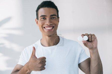 Photo pour Beau jeune homme tenant conteneur pour lentille de contact et montrant pouce vers le haut - image libre de droit