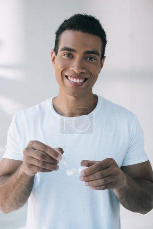 Photo pour Jeune homme souriant et regardant l'appareil-photo tout en mettant la solution d'objectif dans le récipient avec l'objectif - image libre de droit
