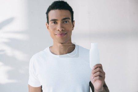 Photo pour Jeune homme retenant la bouteille blanche avec la crème cosmétique et regardant l'appareil-photo - image libre de droit