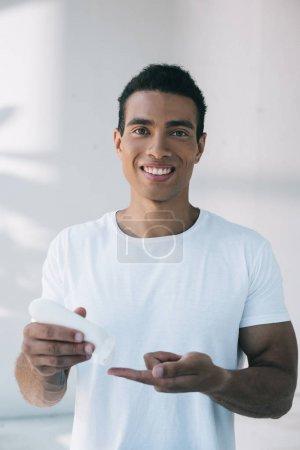 Photo pour Beau jeune homme mettant la crème cosmétique sur le doigt de la bouteille blanche - image libre de droit
