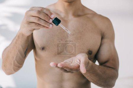 Photo pour Vue recadrée de l'homme laissant tomber le sérum de pipette sur la main - image libre de droit