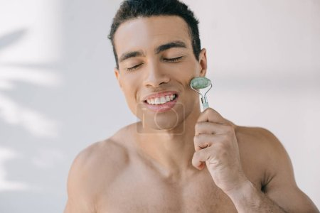 Photo for Handsome mixed race man massaging face with jade roller and smiling with closed eyes - Royalty Free Image