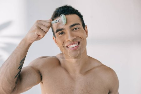 Photo for Handsome mixed race man massaging forehead with jade roller and smiling while looking at camera - Royalty Free Image