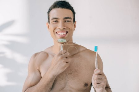 Photo for Handsome mixed race man massaging face with jade roller and holding toothbrush while looking at camera - Royalty Free Image