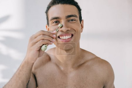 Photo for Muscular mixed race man massaging nose with stone jade roller and smiling while looking at camera - Royalty Free Image