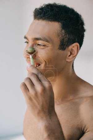 Photo for Muscular mixed race man massaging nose with stone jade roller and smiling while looking away - Royalty Free Image