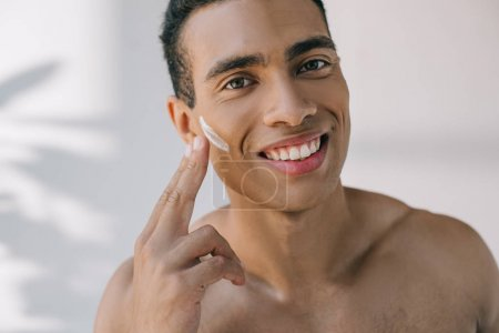portrait shot of handsome man applying cosmetic cream on face with fingers and smiling while looking at camera