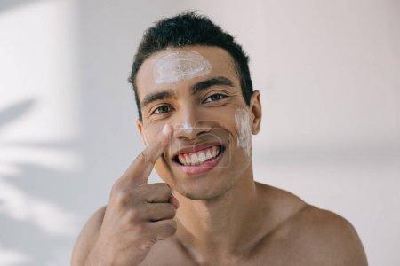 Photo pour Beau homme de race mélangé appliquant la crème cosmétique sur le visage avec le doigt et le sourire tout en regardant loin - image libre de droit