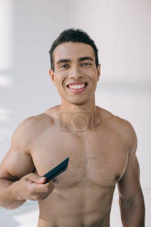 Photo pour Beau homme de course mélangé retenant la brosse à cheveux et souriant tout en regardant l'appareil-photo - image libre de droit
