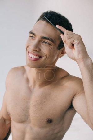 Photo pour Beau homme de course mélangé peignant les cheveux avec la brosse à cheveux et souriant tout en regardant loin - image libre de droit