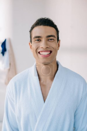 Photo for Handsome man in bathrobe smiling and looking at camera - Royalty Free Image