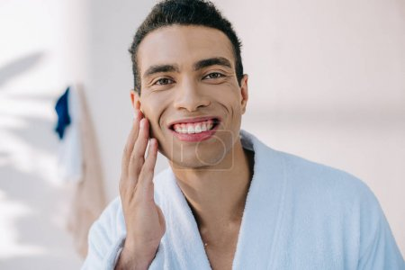 Photo for Handsome man in bathrobe touching face while smiling and looking at camera - Royalty Free Image