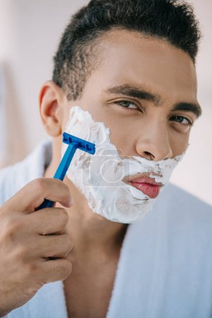 Photo for Portrait shot of handsome man shaving face with razor and looking at camera - Royalty Free Image