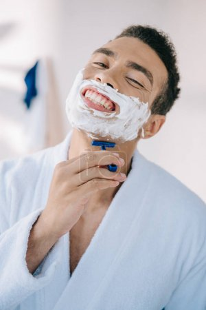 Photo for Portrait shot of handsome man shaving face with razor while smiling and looking at camera - Royalty Free Image
