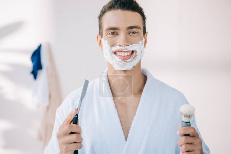 Photo for Handsome young man with shaving cream on face holding razor blade and shaving brush, smiling and looking at camera - Royalty Free Image