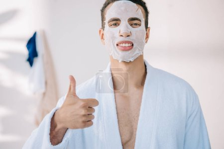 Photo for Young man in bathrobe with face mask showing thumb up and looking at camera - Royalty Free Image
