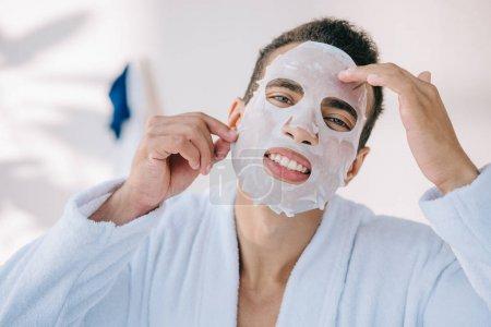 Photo pour Jeune homme dans le peignoir essayant d'enlever le masque de visage tout en regardant l'appareil-photo - image libre de droit
