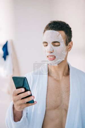 Photo for Young man in bathrobe with cosmetic mask on face holding smartphone - Royalty Free Image
