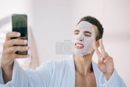 Photo for Young man in bathrobe with cosmetic mask on face taking selfie on smartphone and showing victory sign - Royalty Free Image