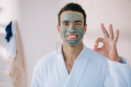 Photo pour Bel homme avec le masque de visage et dans le peignoir affichant le signe correct et regardant l'appareil-photo - image libre de droit