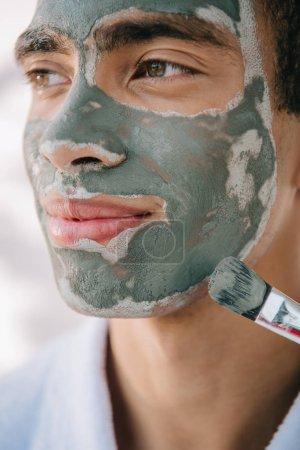 Photo pour Fermer la vue vers le haut de l'homme beau appliquant le masque de visage avec le pinceau et regardant loin - image libre de droit