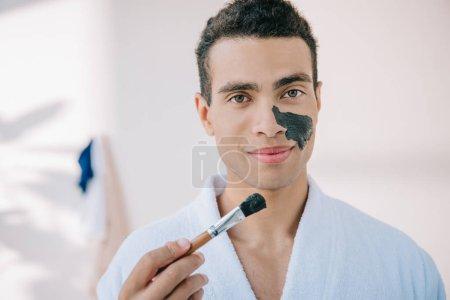 Photo pour Jeune homme beau dans le bol de fixation de peignoir avec le masque de visage et l'appliquant sur le visage avec le pinceau tout en regardant l'appareil-photo - image libre de droit