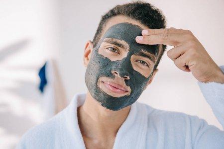 Photo pour Jeune homme confiant appliquant le masque de visage avec des doigts et regardant l'appareil-photo - image libre de droit