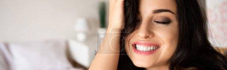 Foto de Foto panorámica de hermosa joven tocando el pelo y sonriendo con los ojos cerrados - Imagen libre de derechos