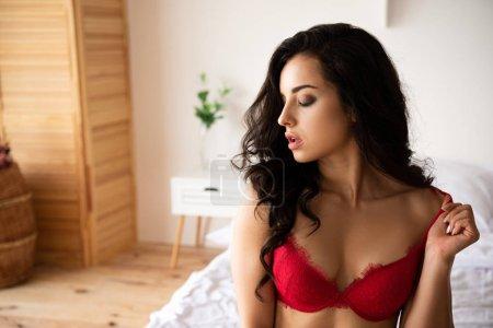 Photo pour Jeune fille sexy dans les sous-vêtements rouges s'asseyant sur le lit avec les yeux fermés - image libre de droit