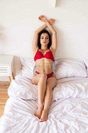 Photo pour Vue pleine longueur de la fille sexy dans les sous-vêtements rouges s'asseyant dans le lit et détendant avec les yeux fermés - image libre de droit
