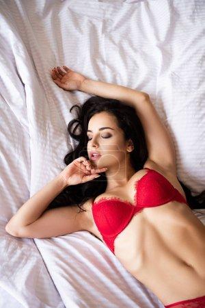 Photo pour Fille sexy dans les sous-vêtements rouges détendant tout en se trouvant dans le lit avec les yeux fermés - image libre de droit