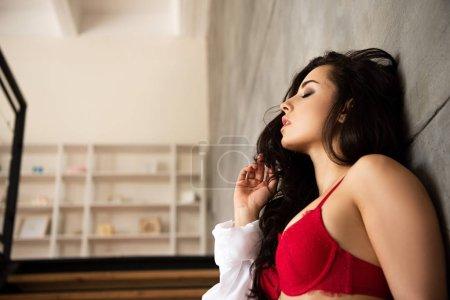 Photo pour Vue de côté de fille sexy dans les sous-vêtements rouges et la chemise blanche se penchant sur le mur gris avec les yeux fermés - image libre de droit