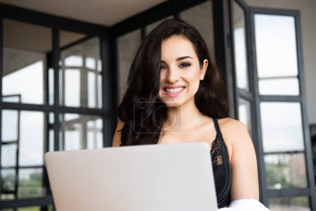 Photo for Sexy girl in black underwear and white shirt using laptop while smiling and looking at camera - Royalty Free Image