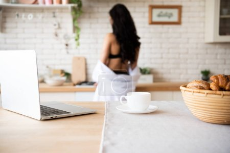 Photo for Selective focus of laptop, cup of coffee and basket with buns on table with girl on background - Royalty Free Image