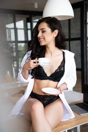 Photo pour Fille sexy dans les sous-vêtements noirs et le café potable de chemise blanche avec les yeux fermés tout en s'asseyant sur la table dans la cuisine - image libre de droit