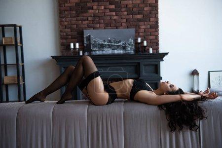 Photo pour Vue latérale de fille sexy en sous-vêtements noirs posant les yeux fermés tout en étant couché sur le canapé dans le salon - image libre de droit