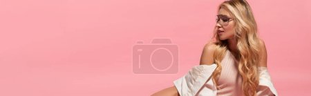 Photo for Panoramic shot of beautiful blonde girl in bodysuit and sunglasses posing on pink - Royalty Free Image