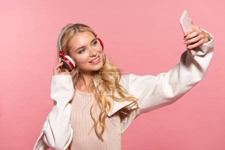 Photo for Beautiful blonde woman with headphones taking selfie on smartphone isolated on pink - Royalty Free Image