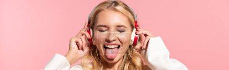 Panoramaaufnahme der schönen blonden Frau mit Kopfhörern und geschlossenen Augen, die die Zunge isoliert auf rosa