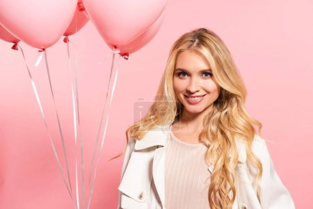 beautiful blonde smiling girl holding pink balloons on pink