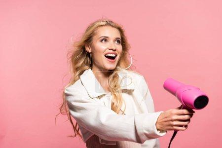 Foto de Sonriendo hermosa mujer rubia sosteniendo secador de pelo aislado en rosa - Imagen libre de derechos