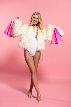 Photo pour Femme blonde belle heureuse dans la veste blanche de fausse fourrure retenant des sacs à provisions sur le rose - image libre de droit